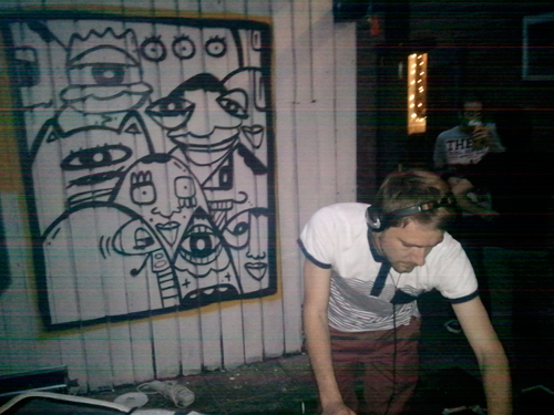DJ Spinning Choons in front of Kev Munday's Art Work